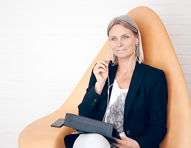 Psykolog sidder i orange designerstol og giver behandling gennem Online terapi hos GoMentor
